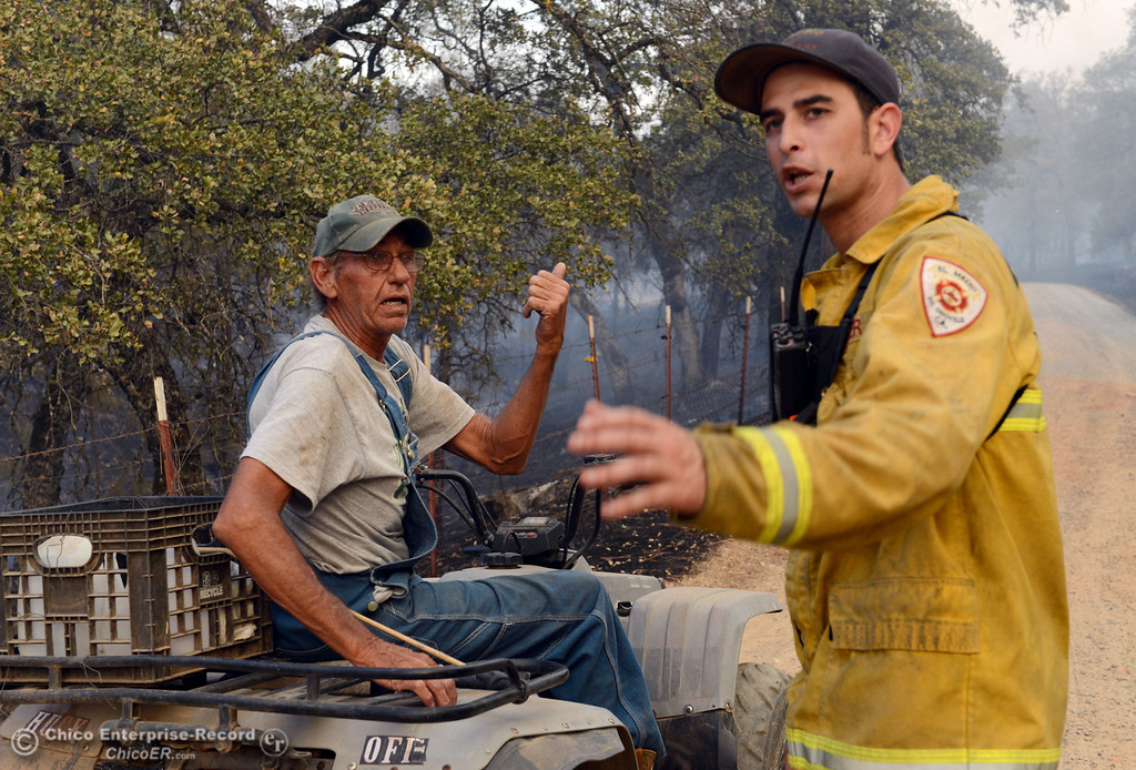 . Glenn Bentley (left) talks to El Medio firefighter Corey Diaz (right) about the flames reaching close to his home along Chinese Wall Road as the Swedes Fire burned along Swedes Flat Road, in the vicinity of Chinese Wall Road, just east or Oro Bangor Highway Friday, August 16, 2013 in Oroville, Calif. Over 200 acres were burned with at least one structure lost. (Jason Halley/Chico Enterprise-Record)