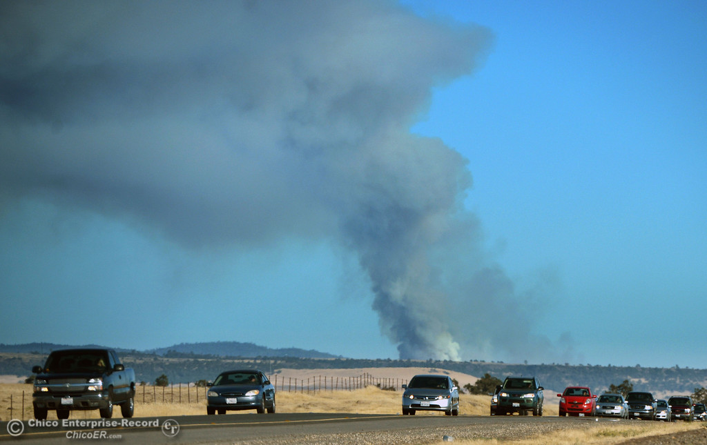 . Cars drive along Highway 99 as the smoke plume from the Swedes Fire can be seen burning just east or Oro Bangor Highway Friday, August 16, 2013 in Oroville, Calif. Over 200 acres were burned with at least one structure lost. (Jason Halley/Chico Enterprise-Record)