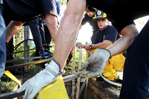 """Mountain View firefighter Ben Carter, center right,  works with other firefighters to rescue a cow that fell into a well on Friday, Oct. 7, at 12166 Jay Rd. in Erie. For more photos and video of the rescue go to  <a href=""""http://www.dailycamera.com"""">http://www.dailycamera.com</a><br /> Jeremy Papasso/ Camera"""