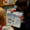 KRISTOPHER RADDER - BRATTLEBORO REFORMER<br /> Brattleboro Firefighter George Allen reads while children gather to listen at Everyone's Books, on Elliot Street, as part of the Twinkle Town events on Sunday, Jan. 14, 2018.