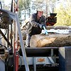 BEN GARVER — THE BERKSHIRE EAGLE<br /> Dicken Crane moves a log off a truck bed onto a firewood processor at Holiday Brook Farm in Dalton, Monday, February 11, 2019.  Crane was working in the afternoon to get as much firewood prepared as possible before the snow.