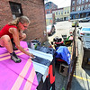 """KRISTOPHER RADDER — BRATTLEBORO REFORMER<br /> Kim Carlino, from Northhampton, Mass., puts the final touches on her mural """"Celestial Charting of a Wandering Line"""" on a shed behind Brown and Roberts Hardware, in Brattleboro, on Tuesday, July 30, 2019."""
