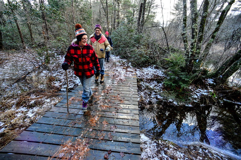 KRISTOPHER RADDER — BRATTLEBORO REFORMER<br /> Laura Williams, of Spofford, N.H., looks at the reflections in the water while walking the Doolittle Trail at Pisgah State Park, in Winchester, N.H., during New Hampshire's First Day Hike on Jan. 1, 2019.  Williams said the First Day Hike sounded good and thought it would be a great way to start 2019.