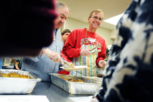 Turkey_2.jpg Volunteers Mark Lewis, left, and Jim Remnant serve turkey at Boulder's First Presbyterian Church's annual Thanksgiving Dinner held on November 22, 2012. The church opens it's doors to the homeless, eldery, shut-ins and anyone in need. They expected to serve between 300-350 people.  (Kira Horvath/Daily Camera)