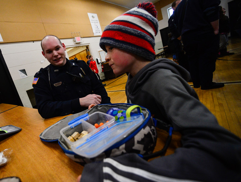 KRISTOPHER RADDER - BRATTLEBORO REFORMER<br /> Brattleboro Police Officer Michael Cable sits down to talk with Henry Schwartz, 9, during the second annual First Responders BBQ Lunch at Oak Grove Elementary on Wednesday, Feb. 14, 2018.