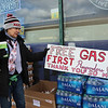 Harry's Food Mart Mobil gas station on Middlesex Street, providing free gas and energy drinks to health care workers and first responders on Good Friday. Volunteer Helene Renaud of Lowell, with sign. (SUN/Julia Malakie)