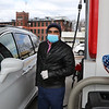 Harry Patel, owner of Harry's Food Mart Mobil gas station on Middlesex Street, pumps gas for a customer as the station provides free gas, as well as free energy drinks, to health care workers and first responders on Good Friday. (SUN/Julia Malakie)