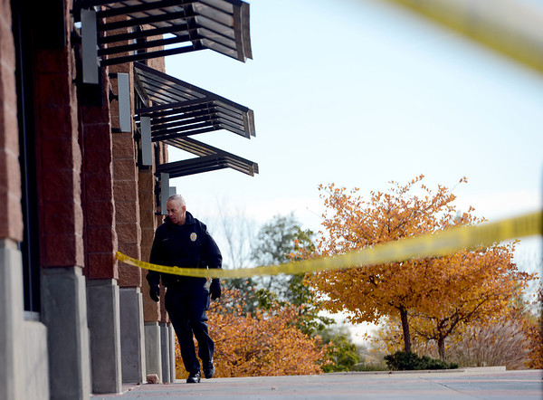 """A Boulder police officer walks around the scene of a bank robbery on October 19, 2012.<br /> Boulder police are looking for a suspect in a bank robbery at a FirstBank in north Boulder just after 9 a.m. Friday morning.<br /> For more photos and video of the bank, go to  <a href=""""http://www.dailycamera.com"""">http://www.dailycamera.com</a>.<br /> Cliff Grassmick  / October 19, 2012"""
