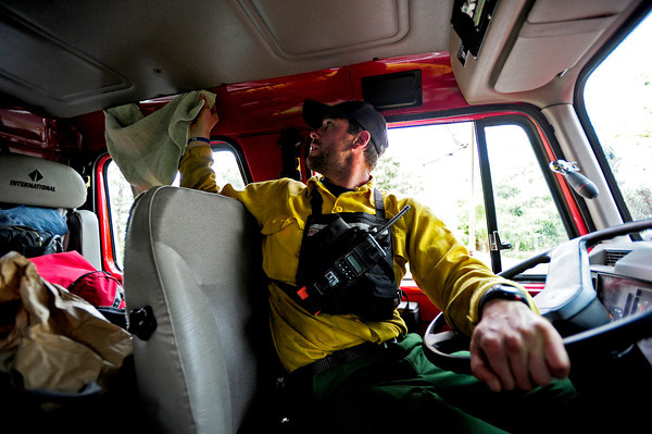 Brent Meyers, of the Missoula Fire department attempts to prevent water from coming inside his truck with a towel while waiting out the rain on Thursday afternoon at Cragmoor Road. Fire trucks have gathered to work on the fire line break to protect the neighborhoods in South Boulder, Colorado. The fire fighters were waiting out the rain in case of lightning strike before going back to work. June 28, 2012. Rachel Woolf/ For the Daily Camera