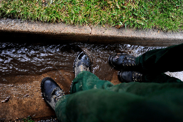 Fire fighters put their feet in the gutter of the road Thursday afternoon as they wait out the rain at Cragmoor Road where fire trucks have gathered to work on the fire line break to protect the neighborhoods in South Boulder, Colorado. The fire fighters were waiting out the rain in case of lightning strike before going back to work. June 28, 2012. Rachel Woolf/ For the Daily Camera