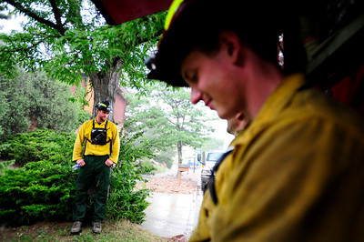 Brent Meyers, left, of the Missoula Fire department stands under a tree to stay out of the rain on Thursday afternoon while Philip Keating, and others hide under the cover of the fire truck at Cragmoor Road in Boulder where several departments have gathered to work on the fire line break to protect the neighborhoods in South Boulder, Colorado from Flagstaff fire. The fire fighters were waiting out the rain in case of lightning strike before going back to work. June 28, 2012. Rachel Woolf/ For the Daily Camera