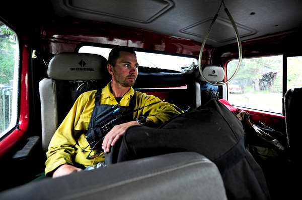 Philip Keating, of the Missoula Fire department looks out the window from his fire truck while waiting out the rain on Thursday afternoon at Cragmoor Road where fire trucks have gathered to work on the fire line break to protect the neighborhoods in South Boulder, Colorado.  The fire fighters were waiting out the rain in case of lightning strike before going back to work. June 28, 2012. Rachel Woolf/ For the Daily Camera