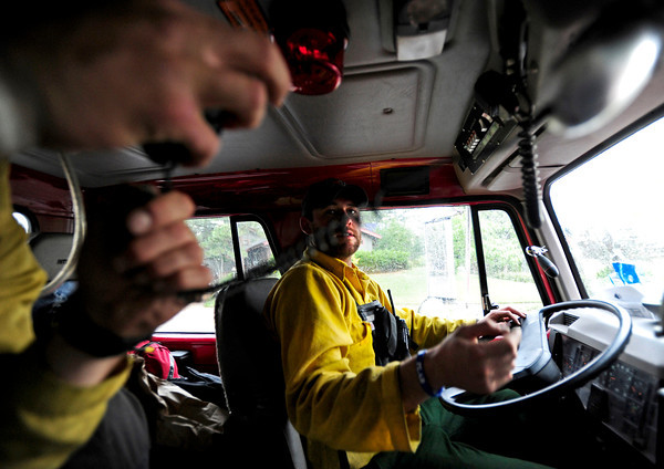 Brent Meyers looks to the hands of Philip Keating, both of the Missoula Fire department while Keating attempts to answer a phone while waiting out the rain on Thursday afternoon at Cragmoor Road. Fire trucks have gathered to work on the fire line break to protect the neighborhoods in South Boulder, Colorado. The fire fighters were waiting out the rain in case of lightning strike before going back to work.<br /> June 28, 2012. Rachel Woolf/ For the Daily Camera
