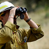 A fire fighter who preferred to be unidentified looks up through binoculars to the Ironing Board Fire on Green Mountain from the base of the trailhead at Cragmoor Road where fire trucks have gathered to work on the fire line break to protect the neighborhoods in South Boulder, Colorado. June 28, 2012. Rachel Woolf/ For the Daily Camera