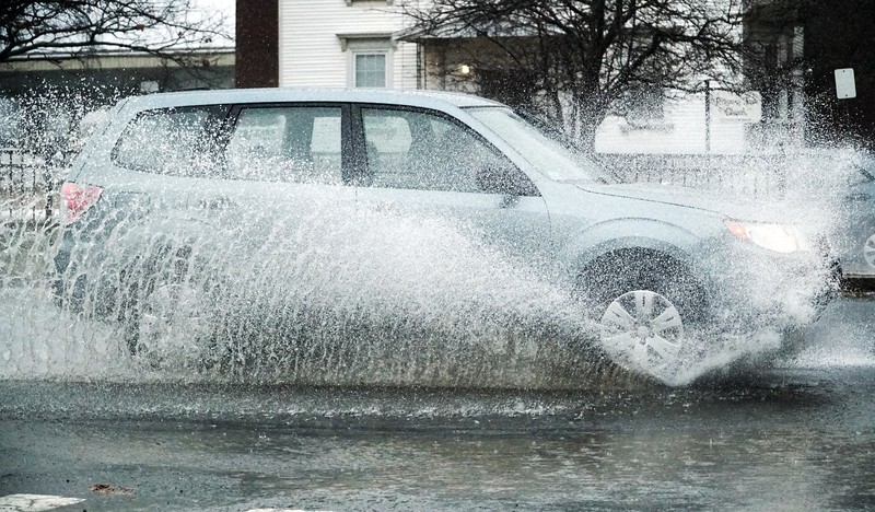 BEN GARVER – THE BERKSHIRE EAGLE<br /> An SUV drives through standing water on East Street in Pittsfield, Friday, January 12, 2018. Heavy rains and snow melt are causing flooding.