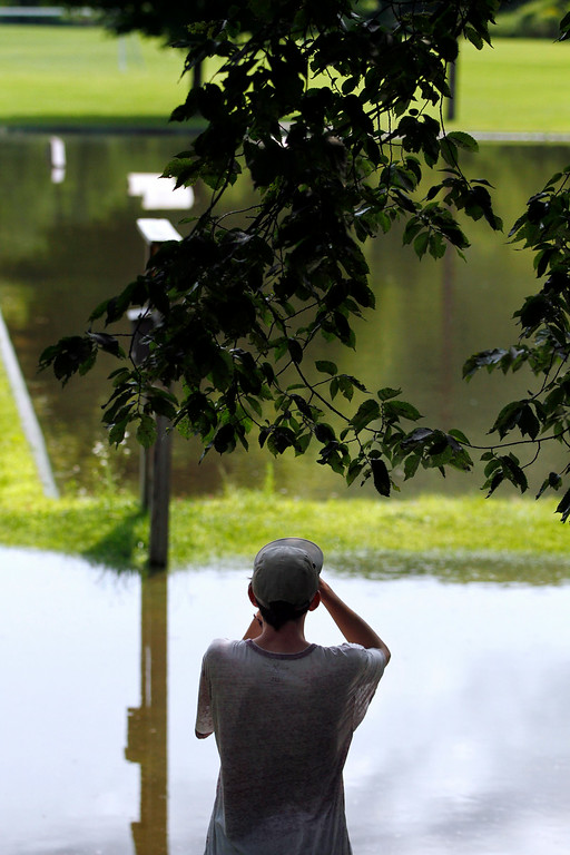 . A passer-by takes a photo of the flooded skate park in Stockbridge due to recent heavy rains. Tuesday, July 29, 2014. Stephanie Zollshan / Berkshire Eagle Staff / photos.berkshireeagle.com