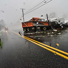 KRISTOPHER RADDER — BRATTLEBORO REFORMER<br /> A Brattleboro police officer closes down a section of Route 9, near Leader Home Center, as crews try to remove debris from the roadway to allow the water to flow freely.