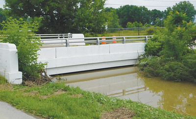JONATHAN DELOZIER / GAZETTE Water rests mere inches below a Rittman bridge Monday after weekend rains left areas flooded.