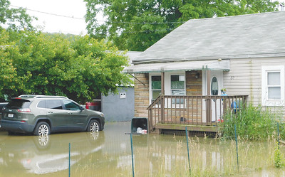 JONATHAN DELOZIER / GAZETTE Floodwaters cover up several front yards Monday on Thonen Street in Rittman.
