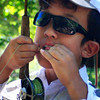 Braneon Roberts, 10, ties on a new fly while fishing Boulder Creek near Eben G. Fine Park on Friday, July 16, during his fly fishing class through Thorne Nature Science School.<br /> Greg Lindstrom / The Camera