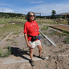 "Lynn Walker stands over the foundation of the family home that burned in the fire last year.<br /> Mike and Lynn Walker of Colorado Mountain Ranch lost their home and other buildings in the Four Mile Canyon Fire.<br /> For a video and photos of Colorado Mountain Ranch, go to  <a href=""http://www.dailycamer.com"">http://www.dailycamer.com</a>.<br /> Cliff Grassmick / August 26, 2011"