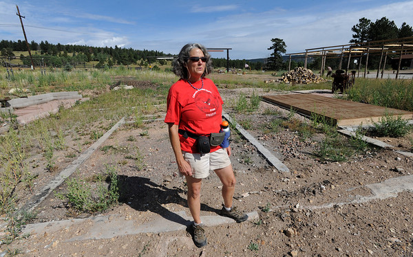 """Lynn Walker stands over the foundation of the family home that burned in the fire last year.<br /> Mike and Lynn Walker of Colorado Mountain Ranch lost their home and other buildings in the Four Mile Canyon Fire.<br /> For a video and photos of Colorado Mountain Ranch, go to  <a href=""""http://www.dailycamer.com"""">http://www.dailycamer.com</a>.<br /> Cliff Grassmick / August 26, 2011"""