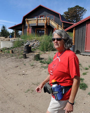 "Lynn Walker walks past the new barn that replaced the one lost in the fire last year.<br /> Mike and Lynn Walker of Colorado Mountain Ranch lost their home and other buildings in the Four Mile Canyon Fire.<br /> For a video and photos of Colorado Mountain Ranch, go to  <a href=""http://www.dailycamer.com"">http://www.dailycamer.com</a>.<br /> Cliff Grassmick / August 26, 2011"