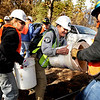 "Nicole Palestro, of Frederick, right, works with Carly Anderson, of Philidelphia, center to free one seeding bucket from another on Saturday, March 19, during a volunteer seeding effort on Salina Mountain Rd. in the Fourmile Canyon area of Boulder. The volunteers are trying to re-grow the burned vegetation in the area caused by the Fourmile Canyon wildfire. For more photos go to  <a href=""http://www.dailycamera.com"">http://www.dailycamera.com</a><br /> Jeremy Papasso/ Camera"