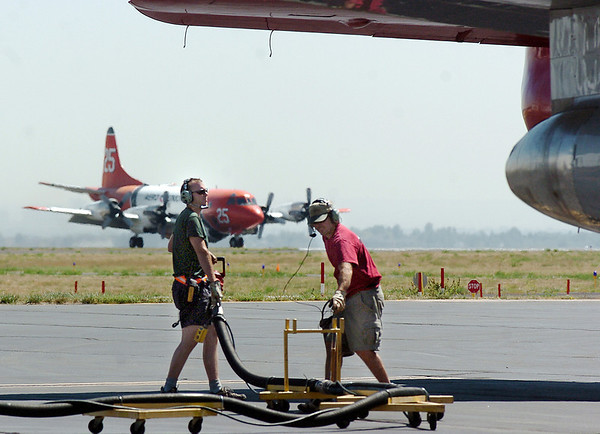 Will Leininger, left, and Steve Wood, retardant loading crew, move a hose away from an airtanker at the US Forest Service Airtanker base at Rocky Mountain Metro Airport as a P-3 airtanker lands behind them while fighting the Four Mile fire in Boulder County on Tuesday. <br /> <br /> September 7, 2010<br /> staff photo/David R. Jennings