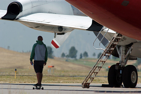 Co-pilot Gary Thomas skate boards to his P-3 airtanker at the US Forest Service Airtanker base at Rocky Mountain Metro Airport while waiting to fight the Four Mile Canyon Fire in Boulder County on Tuesday. <br /> September 7, 2010<br /> staff photo/David R. Jennings