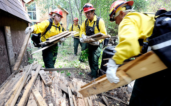 Fire fighters from Rosebud South Dakota remove fire old wood and debris from around a home in the Fourmile Canyon fire area in Boulder, Colorado September 9, 2010.  CAMERA/Mark Leffingwell (POOL)