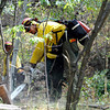 Pierre Blue Thunder, from Rosebud, South Dakota cuts away small trees from around a storage shed in the Fourmile Canyon fire in Boulder, Colorado September 9, 2010.  CAMERA/Mark Leffingwell (POOL)