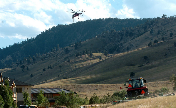 "One of the water dropping helicopters flies over a grass cutting operation near 2nd Street and Dakota Blvd.<br /> The City of Boulder Open Space and Mountain Parks had crews cutting the high dry grass in northwest Boulder near the edge of residential areas.<br /> For  videos  and photos relating to the fire,  go to  <a href=""http://www.dailycamera.com"">http://www.dailycamera.com</a>.<br /> Cliff Grassmick / September 9, 2010"