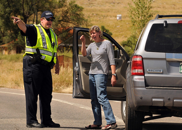 Boulder Police Officer Scott Adams holds the keys of Boulder resident after she tried to drive past the checkpoint on Thursday, Sept. 9, on Lee Hill Road in Boulder. The officers at the checkpoint were denying entry to residents due to danger from the high winds. The resident was trying to get back to her house to gather some personal belongings.<br /> Jeremy Papasso/ Camera