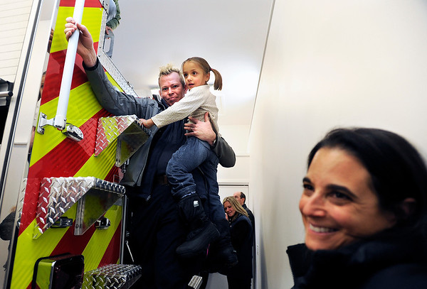"Fourmile firefighter Matthew Walker-Bannon, left, helps Wren Hybretson, 6, down from the back of the new fire truck during the opening ceremony for the new Fourmile Fire Department's Salina Fire Station on Saturday, Dec 3, in the Fourmile Canyon area of Boulder County. The fire station was destroyed in the Fourmile Canyon fire. For more photos and video of the ceremony go to  <a href=""http://www.dailycamera.com"">http://www.dailycamera.com</a><br /> Photo by Jeremy Papasso"