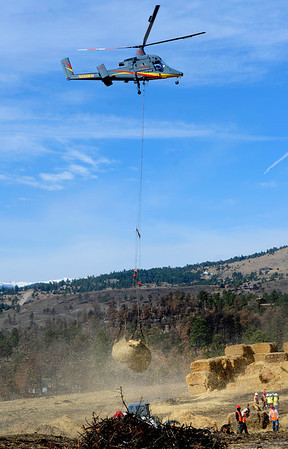 "MULCH<br /> A K-Max helicopter hovers while workers fill a net with straw mulch material to deposit on the Fourmile Fire burn area on Thursday. The county project will reduce flooding threats in the most severely burned areas. For a video of the project, see  <a href=""http://www.dailycamera.com"">http://www.dailycamera.com</a>.<br /> Photo by Marty Caivano/April 7, 2011"