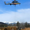MULCH<br /> A K-Max helicopter hovers while workers fill a net with straw mulch material to deposit on the Fourmile Fire burn area on Thursday. The county project will reduce flooding threats in the most severely burned areas.<br /> <br /> Photo by Marty Caivano/April 2, 2011