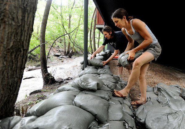 """Julie Gauff, right, and Alex Green put up a wall of sandbags at their Fourmile Canyon residence of Thursday.<br /> For a video of flood preparation, go to  <a href=""""http://www.dailycamera.com"""">http://www.dailycamera.com</a>.<br /> Cliff Grassmick / July 14, 2011"""