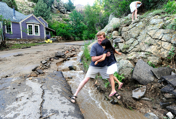 "FLOOD.JPG FLOOD<br /> David Reed helps Piper Yun, 7, across a channel of water running down Fourmile Canyon Drive from the culverts at the intersection with Gold Run Road on Thursday afternoon. Reed heavily sandbagged his cabin near this spot, and it stayed dry during a flood of the entire intersection. For a video with Reed, see  <a href=""http://www.dailycamera.com"">http://www.dailycamera.com</a>.<br /> Photo by Marty Caivano/July 14, 2011"