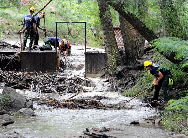 """Fourmile Fire Crew members clean the branches and mud out of Boulder Creek at the Boulder Mountain Lodge up Fourmile Canyon.<br /> For a video of flood preparation, go to  <a href=""""http://www.dailycamera.com"""">http://www.dailycamera.com</a>.<br /> Cliff Grassmick / July 14, 2011"""