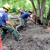 "Shanti Leasure, left, along with other Fourmile Fire Crew members, clean the branches and mud out of Boulder Creek at the Boulder Mountain Lodge up Fourmile Canyon.<br /> For a video of flood preparation, go to  <a href=""http://www.dailycamera.com"">http://www.dailycamera.com</a>.<br /> Cliff Grassmick / July 14, 2011"