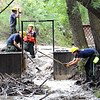 "Fourmile Fire Crew members clean the branches and mud out of Boulder Creek at the Boulder Mountain Lodge up Fourmile Canyon.<br /> For a video of flood preparation, go to  <a href=""http://www.dailycamera.com"">http://www.dailycamera.com</a>.<br /> Cliff Grassmick / July 14, 2011"