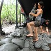 "Julie Gauff and Alex Green put up a wall of sandbags at their Fourmile Canyon residence of Thursday.<br /> For a video of flood preparation, go to  <a href=""http://www.dailycamera.com"">http://www.dailycamera.com</a>.<br /> Cliff Grassmick / July 14, 2011"