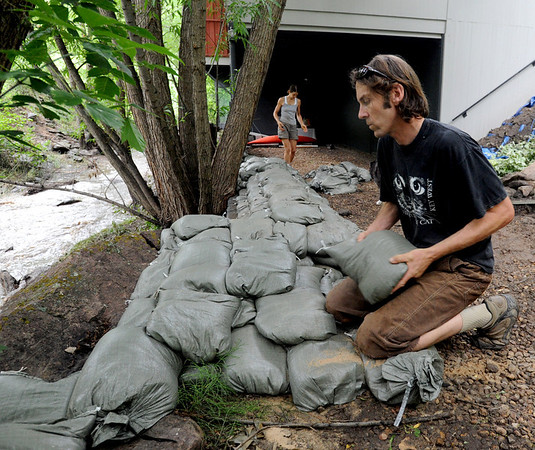 "Julie Gauff, back left, and Alex Green put up a wall of sandbags at their Fourmile Canyon residence of Thursday.<br /> For a video of flood preparation, go to  <a href=""http://www.dailycamera.com"">http://www.dailycamera.com</a>.<br /> Cliff Grassmick / July 14, 2011"