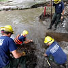 "Sam Robinson, center, along with other Fourmile Fire Crew members, clean the branches and mud out of Boulder Creek at the Boulder Mountain Lodge up Fourmile Canyon.<br /> For a video of flood preparation, go to  <a href=""http://www.dailycamera.com"">http://www.dailycamera.com</a>.<br /> Cliff Grassmick / July 14, 2011"