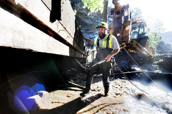 "Matt Linton with a Boulder County Road crew work to clear debris from under a bridge in Fourmile Canyon.<br /> For a video of of the Fourmile storm damage go to  <a href=""http://www.dailycamera.com"">http://www.dailycamera.com</a><br /> Photo by Paul Aiken / The Camera"