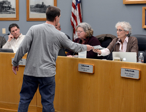 Cliff Willmeng, of Lafayette, hands a petition against fracking signed by several members of the community to Lafayette Mayor Carolyn Cutler during a city council meeting on Tuesday, March 5, at the Lafayette City Hall.<br /> Jeremy Papasso/ Camera