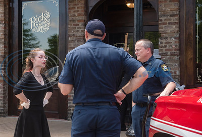 "Rick's on the Square employee Tristen Mullins talks with members of the Tyler Fire Department during a special promotion for Tyler area first responders to receive free meals on Thursday, April 23, 2020. All law enforcement officers and fire department and EMS personnel who showed up wearing a uniform at three Tyler restaurants: Hollytree Country Club, Rick's on the Square and Dakota's, received a free meal sponsored by Tobacco Junction. Tony Cooper, owner of Tobacco Junction said that the free food is a way for Tobacco Junction and the participating eateries to ""show our collective appreciation for the hard work these amazing men and women are doing."""