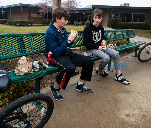 Zane Traylor, 12, and Roger Chrietzberg, 12, eat free lunches outside of Hubbard Middle School in Tyler, Texas on Monday, March 16, 2020. While schools are shut down because of the coronavirus, Tyler Independent School District Food Services is providing free curbside meals at designated school campuses from March 16-20. to all Tyler ISD students.