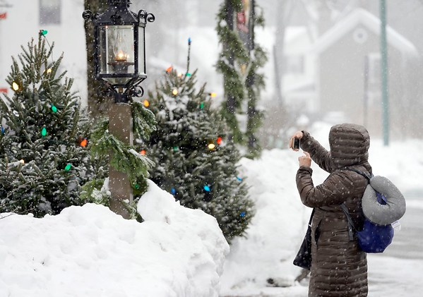 BEN GARVER — THE BERKSHIRE EAGLE<br /> Claudia Gallant of Sandiego takes photographs as the snow begins to fall in Stockbridge, Friday, December 6, 2019. Gallant is visiting for the weekend to see Stockbridge Main Street at Christmas.